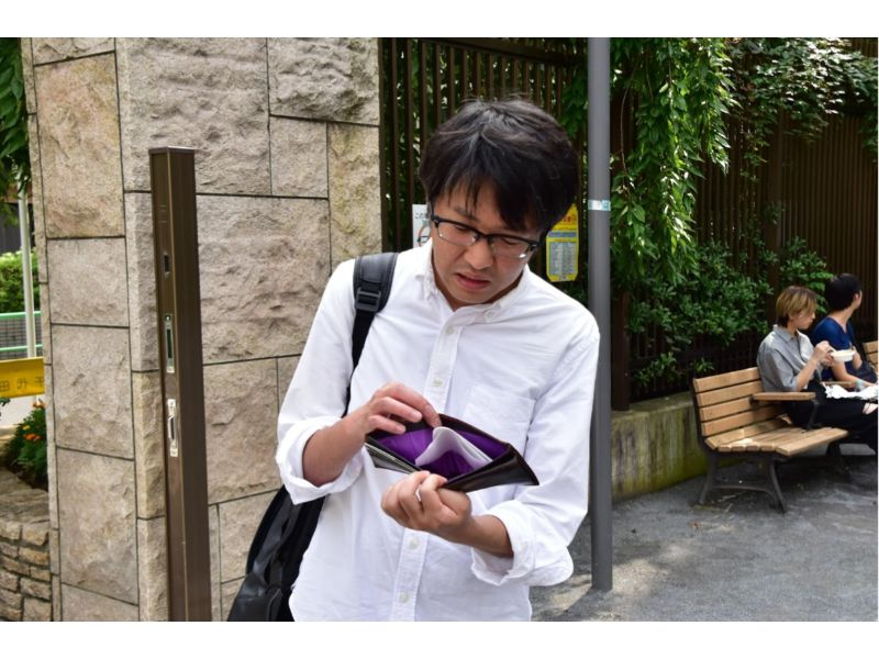 カラの財布を見せる人